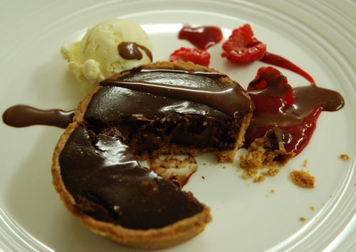 Warm Amedei '9' chocolate tart with raspberry sauce and vanilla ice cream